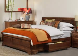 Panelled Sleigh Bed with orange Bedding and Wood Furniture